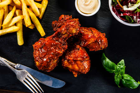 Barbecued drumsticks with french fries and vegetable salad served on black stone on wooden table Stock Photo