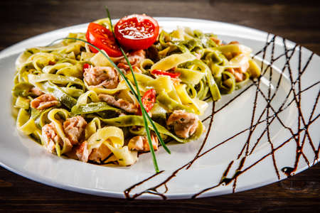 Pasta with salmon and vegetables on wooden table