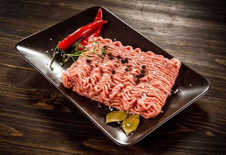 Raw minced pork on wooden background