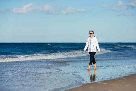 Woman waking on beach