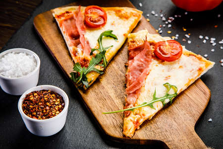 Slices of pizza with ham and vegetables on wooden table
