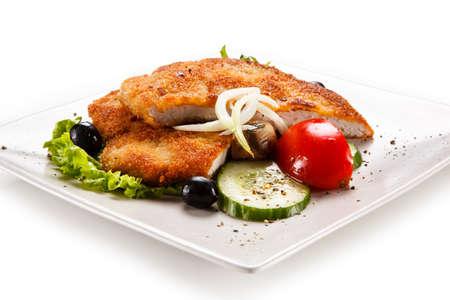 Fried pork chop and vegetable salad on white background