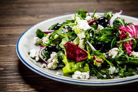 Salad with cottage cheese on wooden background Stock Photo