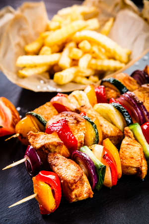Kebabs - grilled meat with french fries and vegetables on wooden background Stock Photo