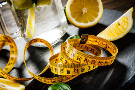 Lemonade with measuring tape on wooden table