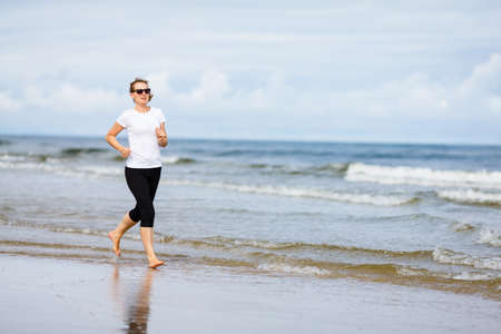 Middle-aged woman running on beach Stock Photo