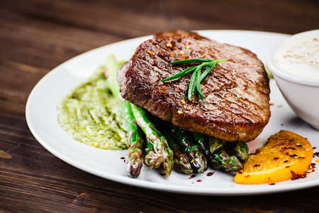 Grilled beefsteak with asparagus on wooden background