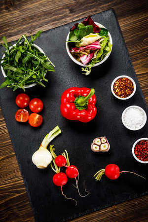 Ingredients for vegetable salad on black stone plate on wooden background