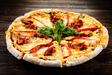 Pizza with ham and pepper on wooden table Фото со стока