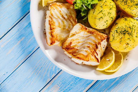 Fried fish with potatoes on wooden table Stock Photo