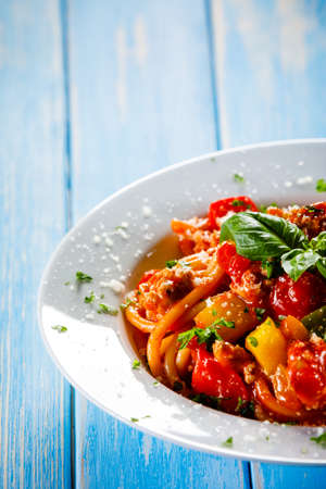 Pasta with meat, tomato sauce and vegetables on wooden table