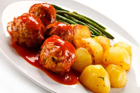 Roast meatballs with potatoes and green beans on white background Foto de archivo - 114760651