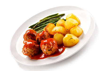 Roast meatballs with potatoes and green beans on white background Foto de archivo - 114760543
