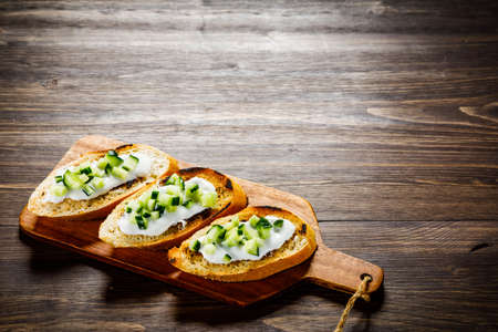Bruschettas on cutting board on wooden background Foto de archivo - 114760209
