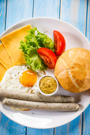 English breakfast - fried egg, sausages, bun and vegetables Standard-Bild