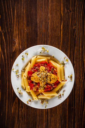 Pasta with chicken meat and sauce on wooden background