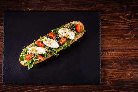 Long sandwich on black stone plate Reklamní fotografie