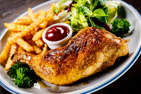 Roasted chicken leg with french fries and vegetable salad on wooden background 스톡 콘텐츠 - 114975135