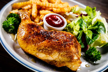 Roasted chicken leg with french fries and vegetable salad on wooden background 스톡 콘텐츠 - 114975144