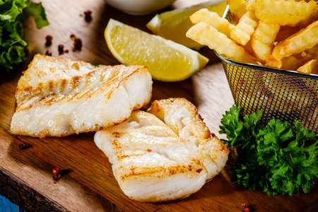 Fish dish - fried fish fillet french fries and vegetables on cutting board on wooden table 스톡 콘텐츠 - 114976040
