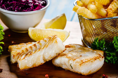 Fish dish - fried fish fillet french fries and vegetables on cutting board on wooden table Stock Photo