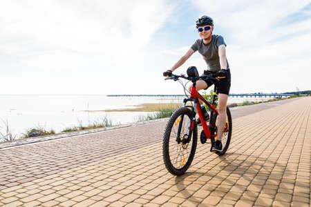 Young man biking at seaside Imagens