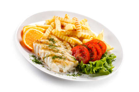 Fish dish - fried fish fillet and vegetables Imagens