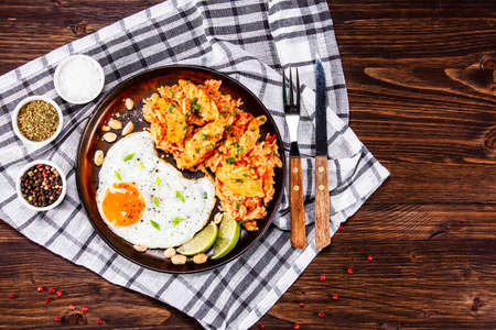 Grilled chicken meat with pork and fried egg on wooden table Stock Photo