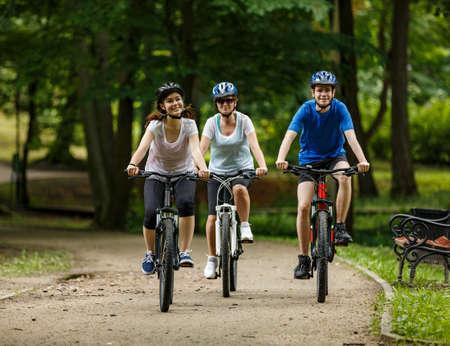 Estilo de vida saludable: personas que andan en bicicleta en el parque de la ciudad