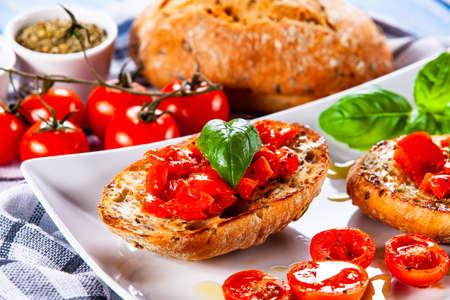 Bruschettas on plate on wooden background Foto de archivo - 120573545