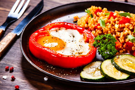 Fried egg, groats and vegetables on wooden table Stockfoto