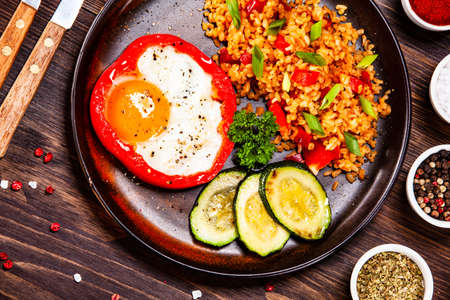 Huevo frito, cereales y verduras en la mesa de madera