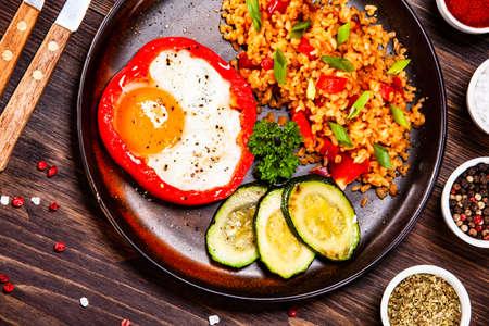 Oeuf au plat, gruau et légumes sur table en bois