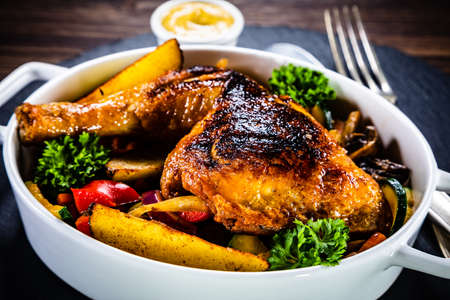 Grilled chicken legs with salad on black stone plate