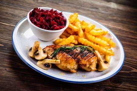 Grilled chicken fillet with french fries and vegetables
