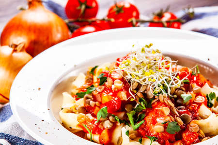 Pasta with tomato sauce and vegetables on wooden table
