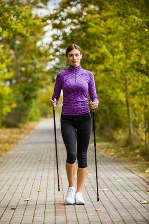 Nordic walking - young woman training Stock Photo