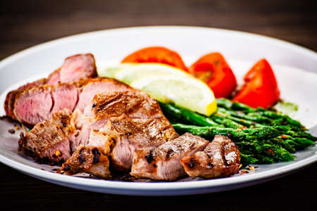 Grilled steak with asparagus on white background