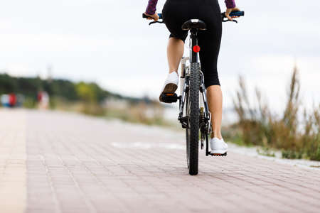 Young woman cycling Imagens