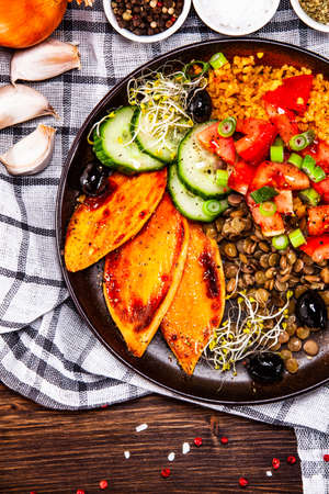 Groats with lentils and vegetables on wooden table Фото со стока
