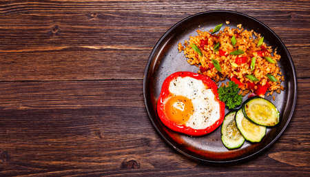 Fried egg, groats and vegetables on wooden table Stock Photo