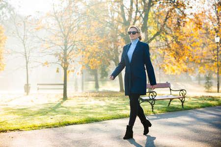 Middle-aged woman walking in city park Reklamní fotografie