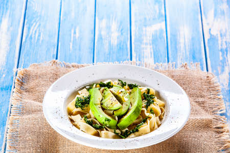 Pasta with avocado on wooden table 免版税图像