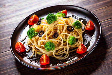 Pasta with herbs and vegetables on wooden background 免版税图像