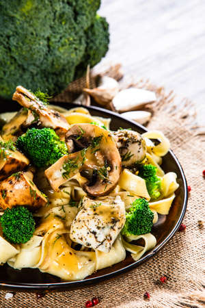 Pasta with chicken and champignon on wooden background