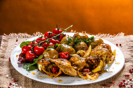 Roast chicken wings, baked potatoes and vegetables Stock Photo