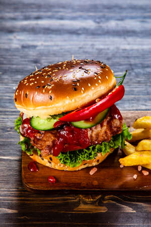 Tasty burger with chips served on cutting board Stockfoto - 129243468