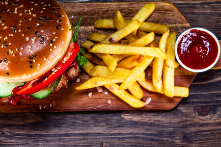 Tasty burger with chips served on cutting board Stockfoto - 129243581