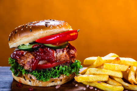 Tasty burger with chips served on cutting board Stockfoto - 129243582