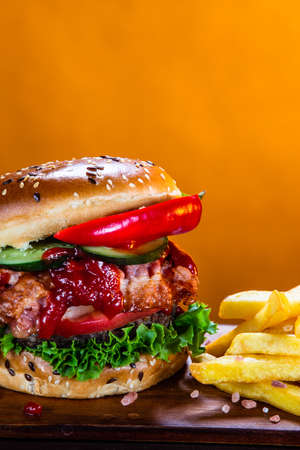 Tasty burger with chips served on cutting board Stockfoto - 129243587